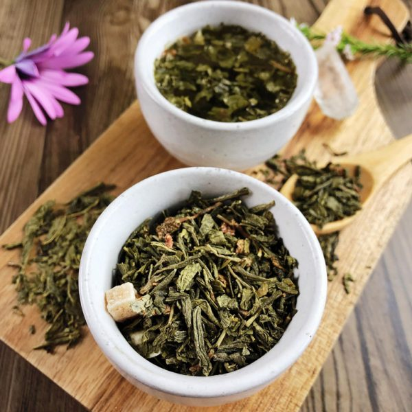 Faerie Garden green tea leaves with papaya and strawberry pieces, dry and steeped in a teacup