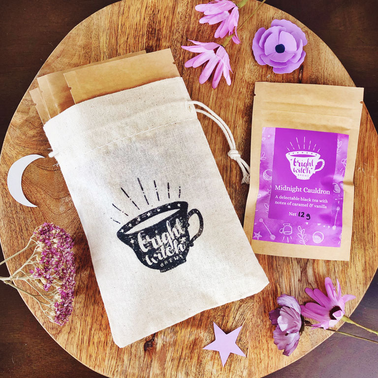 Bright Witch Favourite's Tea Bundle. Image shows a small cotton drawstring bag stamped with the Bright Witch teacup logo, with four tea taster sachets.