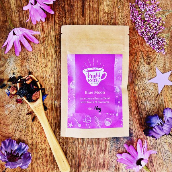 Image shows a Blue Moon herbal blend taster sachet, and teaspoon heaped with loose blend.