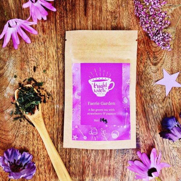 Image shows a Faerie Garden green tea taster sachet, and teaspoon heaped with loose tea blend.