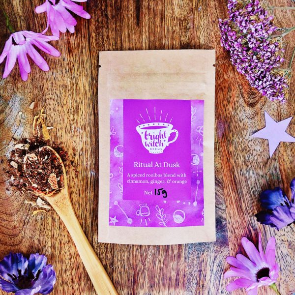 Image shows a Ritual At Dusk rooibos & spices tea taster sachet, and teaspoon heaped with loose tea blend.