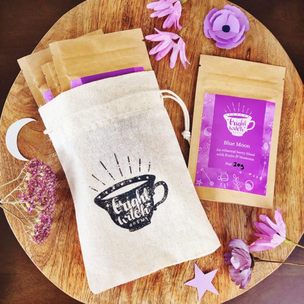 Bright Witch Herbal hearth Tea Bundle. Image shows a small cotton drawstring bag stamped with the Bright Witch teacup logo, with four tea taster sachets.